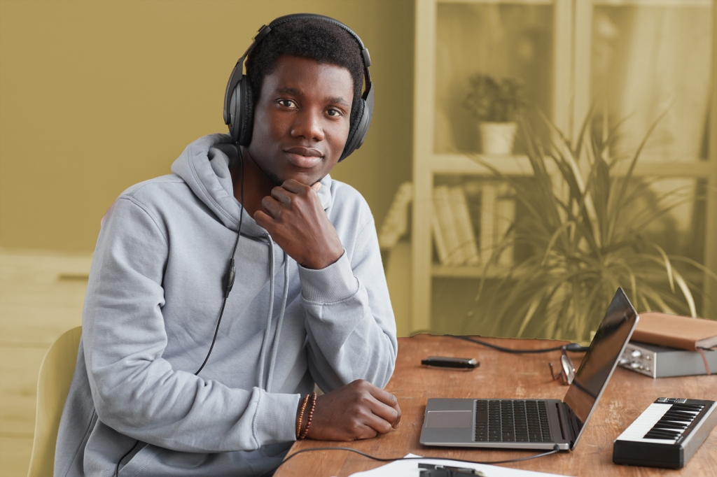 Young man with headphones sitting at a desk listening to beats