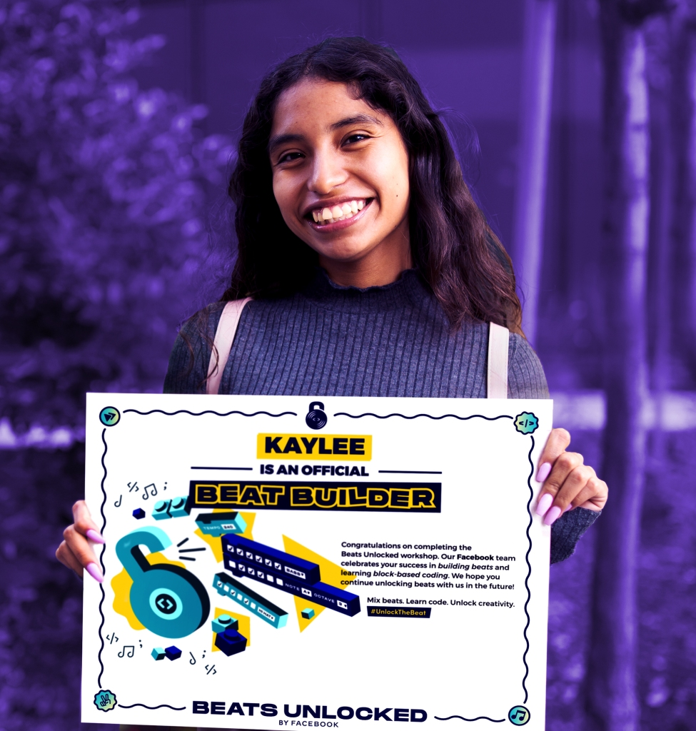A diverse young high school girl holding a Beats Unlocked certificate of completion